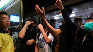 Anti-extradition bill demonstrators block a Mass Transit Railway (MTR) train