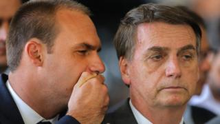Eduardo whispering to his father, Jair Bolsonaro, at a conference in November