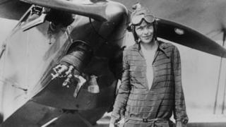 Amelia Earhart in front of a plane
