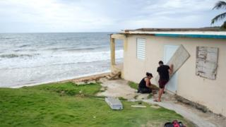 A couple boards up the door of their beachfront house as Tropical Storm Dorian approaches in Yabucoa, Puerto Rico