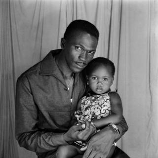 A man and baby girl pose for the camera in the photographer's studio.