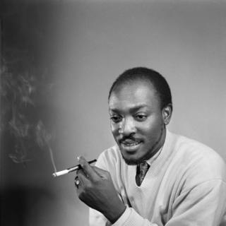 Roger DaSilva poses for a self-timed photograph with a cigarette in hand.