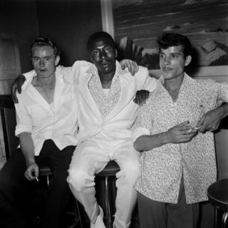 Three men dressed in loose shirts and holding cigarettes stand by the bar.