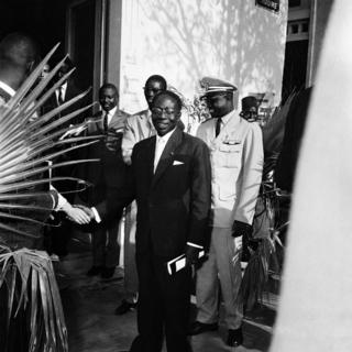 Security personnel flank Léopold Sédar Senghor, then-president of Senegal, who shakes hands with an unseen man.