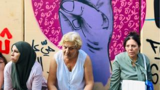 Women sit in front of protest graffiti in Beirut
