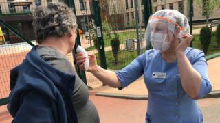 Man has his temperature taken outside care home in Moscow