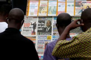 People stand in front of a news stand full of front pages reporting the death of the prime minister.