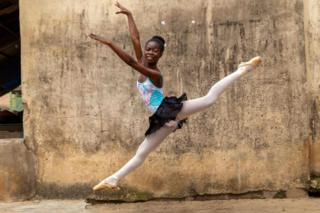 A teenage girl performs a ballet jump outside the classroom.
