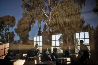Secondary students sit in a classroom. The trees outside are reflected on the window pane.