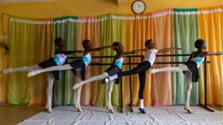 Young dancers dressed in matching leotards hold a ballet barre during a class.